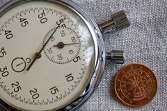 Euromynt med en valör av två eurocent (tillbaka sida) och stoppuren på den vita linbakgrunden - affärsbakgrund Fotografering för Bildbyråer