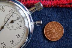 Euromynt med en valör av två eurocent (tillbaka sida) och stoppuren på sliten blå grov bomullstvill med den röda bandbakgrunden - Royaltyfri Bild