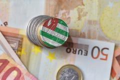 Euromynt med nationsflaggan av Abchazien på bakgrunden för europengarsedlar Royaltyfri Fotografi