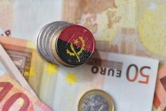 Euromynt med nationsflaggan av Angola på bakgrunden för europengarsedlar Arkivbild