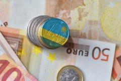 Euromynt med nationsflaggan av Rwanda på bakgrunden för europengarsedlar Royaltyfri Fotografi