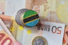 Euromynt med nationsflaggan av Tanzania på bakgrunden för europengarsedlar Fotografering för Bildbyråer