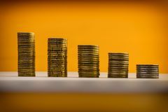 Euromynt och eurocents som staplas på en gul bakgrund Euro mo Royaltyfri Foto