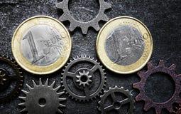 Euromynt och kugghjul arkivfoton