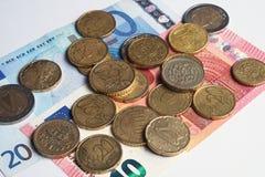 Euromynt och sedlar fördelade på en vit yttersida Arkivbild