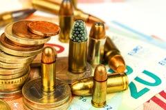 Euromynt och sedlar och kassetter av den olika kalibern Olaglig handel i ammunitionar Sale av vapen Finansiera terrorism arkivfoto
