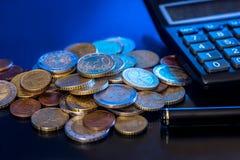 Euromynt och sedlar med räknemaskinen, penna Arkivfoto