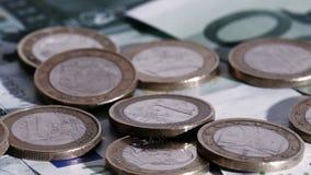 Euromynt som ner faller på eurosedlar arkivfilmer