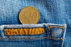 Euromyntet med en valör av cent för euro tio i facket av sliten blå grov bomullstvilljeans med apelsinen snör åt Arkivfoton