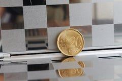 Euromyntet med en valör av 20 eurocent i spegel reflekterar plånboken, rutig bakgrund Royaltyfri Bild