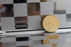 Euromyntet med en valör av 50 eurocent i spegel reflekterar plånboken, rutig bakgrund Royaltyfri Fotografi