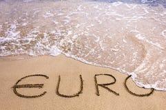 Euroord som är skriftligt i sanden på en strand som bort tvättas av havsvatten Royaltyfri Foto
