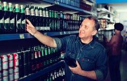 Europäer, der im Supermarkt ein Bier vorwählt Lizenzfreie Stockbilder