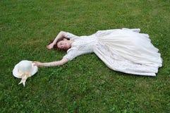 Europäische Frau, die auf Gras legt und ihren Hut im Weinlesekleid im Park berührt Lizenzfreies Stockfoto