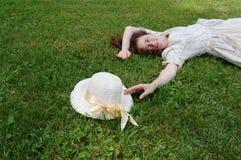Europäische Frau, die auf Gras legt und ihren Hut im Weinlesekleid im Park berührt Stockfotos