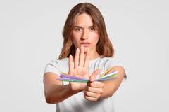 Europäische Frau mit ernstem Ausdruck, Griffplastikstrohe, lehnt Wegwerfplastiktrinkhalme zugunsten metallischen ab, lizenzfreies stockbild