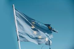 Europäische Gemeinschaft zwölf spielen die zerrissene und mit Flagge Knoten im Wind auf Hintergrund des blauen Himmels die Hauptr lizenzfreie stockfotos
