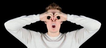 Europäische Junge überraschten den Mann in den Sonnenbrillen, die in binokularem lokalisiert auf schwarzem Hintergrund schauen Stockbilder