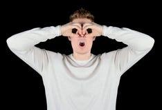 Europäische Junge überraschten den Mann in den Sonnenbrillen, die in binokularem lokalisiert auf schwarzem Hintergrund schauen Lizenzfreie Stockfotos