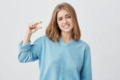Europäische junge Frau, die blaue Strickjacke mit dem blonden Haar an Größe zeigt etwas klein mit den Händen, gestikulierend träg stockfotos