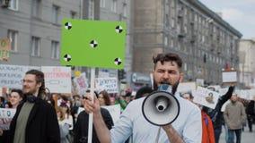 Europäische Leute an der Demonstration Mann mit einer Fahne schreiend in ein Mundstück