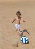 Europäischer Junge, der auf einem sandigen Strand spielt Lizenzfreie Stockbilder