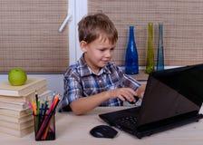 Europäischer Junge am Tisch mit Büchern und Laptop Stockbild