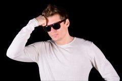 Europäischer junger nachdenklicher Mann in den Sonnenbrillen lokalisiert auf schwarzem Hintergrund Stockbilder