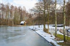 Europäischer Park des Frühjahres mit gefrorenem Kanal Lizenzfreies Stockfoto