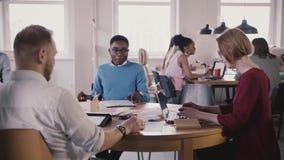 Europäischer weiblicher Chef gibt Führer zu den Angestellten, Arten auf Laptop durch die Tabelle Multiethnische Teamwork bei der  stock footage