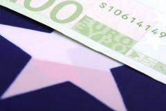 Europäisches Geld auf amerikanischer Flagge Stockfotos