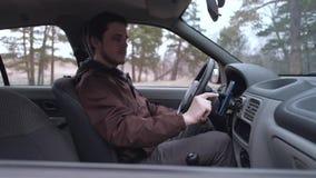 Europ?ischer Manngebrauch Smartphone, sitzend in der Kabine des Autos stock footage
