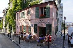 Europa, França, Paris, Montmartre, La Maison, Rose French Cafe - a rua de l'Abreuvoir, pessoa que anda na rua e no carro estacion Fotografia de Stock Royalty Free