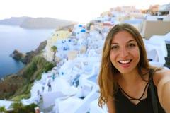 Europa loppselfie som ler flickan i den Oia byn, Santorini Gullig lycklig le turist- flicka som tar självporträttbilden under fotografering för bildbyråer