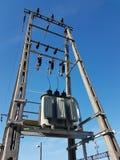 europa País de Polonia Tecnología eléctrica Tranformer del pawer en luz del sol en un fondo del cielo azul Equipo eléctrico de n foto de archivo
