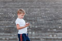 Europe alone a Boy in a white t-shirt enjoys smartphone on ladder . Kids and smart phone, children and the Internet. Europe alone a Boy in a white t-shirt enjoys royalty free stock photography