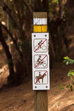 Europe dirt road to pine forest with sign limiting enter by bicycle, horseback, motorcycle. On foot only Stock Images