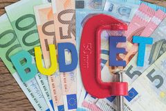 Europe finance, economic, money squeezing idea, colorful alphabe. T word BUDGET using red clamp as G letter on Euro banknotes on wooden table, crisis and world Stock Image
