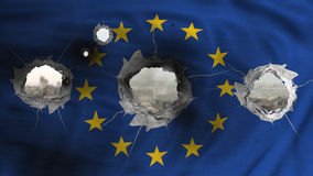 Europe flag waving and perforated , city destroyed on the background Stock Image