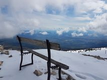 Europe. French Alpes. Mount Ventou of Provence region. A flimsy old bench high in the snow-capped mountains among the clouds. Snow. Cowered mountains Royalty Free Stock Photography