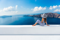 Europe Greece Santorini travel vacation - woman. Europe Greece Santorini travel vacation. Woman looking at view on famous travel destination. Elegant young lady Stock Photos