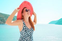 Europe Greece travel vacation. Woman enjoying seaside sunny weather. Young lady living fancy lifestyle wearing red hat on holidays Stock Images