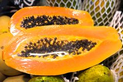 Europe, Spain, Barcelona. The fruit papaya is cut and packaged for sale in the market.  stock images