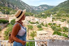 Europe Spain travel vacation. Happy woman in sun hat enjoying at view on village in the Tramuntana mountains. Amazing. View Royalty Free Stock Photo