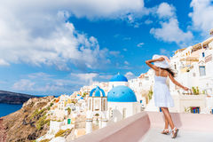 Europe Tourist Travel Woman In Oia Santorini. Europe tourist travel woman in Oia, Santorini, Greece. Happy young woman looking at famous blue dome church Royalty Free Stock Images