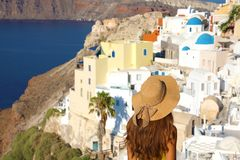 Europe tourist travel woman panorama from Oia, Santorini, Greece. Fashion young woman looking at famous blue dome church landmark. Destination. Beautiful girl royalty free stock images