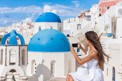 Europe travel woman taking photo Phone Santorini. Europe travel woman taking photo photographing using smart phone in Oia, Santorini, Greece. Famous blue domes Royalty Free Stock Photos