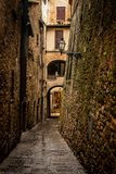 European alley formed of stones. In the background there is a walking human figure. stock photo