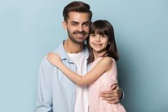 European appearance father and little daughter embracing studio shot stock photo