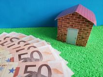 European banknotes, figure of a house on green surface and blue background. Backdrop for mortgage and housing value ads, loan for home construction and stock photo